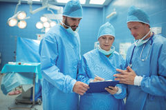 Male and female surgeon discussing over clipboard in operation theater. At hospital Stock Images