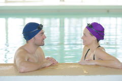 Male and female swimmers chatting at side pool. Male and female swimmers chatting at side of pool Royalty Free Stock Photography