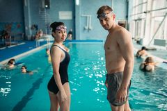 Swimmers puts on a goggles in swimming pool. Male and female swimmers puts on a goggles on workout in swimming pool. Aqua aerobics training, water sport Royalty Free Stock Images