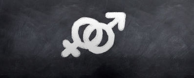 Male and Female Symbols. Written in chalk on a blackboard Royalty Free Stock Photo