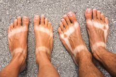 Male and female tanned feet. stock photo