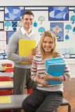 Male And Female Teacher Sitting At Desk. Portrait Of Male And Female Teacher Sitting At Desk In Classroom Stock Photos