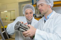 Male and female technicians looking at metal component. Technicians Stock Images
