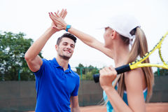 Male and female tennis players gives five Stock Images
