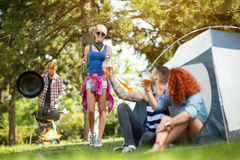 Male and female toasting with glasses of beer with girl at camp Stock Photos