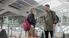 Male and female travelers are communicating in hall of airport, holding suitcase. Man and woman are talking standing in departure hall of airport. They are stock video footage