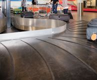 Travelers Waiting For Baggage From Conveyor Belt At Airport Stock Photo