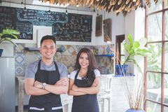 Male and female waitress standing with arms crossed in cafe Royalty Free Stock Photography