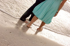 Male and female walking along the beach close up f. A barefoot couple are walking in the sand along the edge of the ocean, Shot from the waist down, They appear Royalty Free Stock Image
