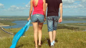 Male and female walking on summer high hill meadow - traveling concept stock footage