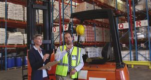 Male and female warehouse managers talking in a warehouse loading bay 4k stock footage