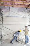Male and female worker standing under scaffold at construction site Royalty Free Stock Images