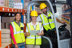 Male and female workers smiling together. In warehouse Stock Images