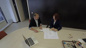 Male and female working together on a blueprint. Workaholic businesswoman and her partner are working together on a project that blueprint on the table with the stock footage