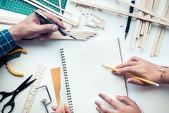 Male and female working on worktable with balsa wood material. Diy,design project,invention concept ideas Stock Photo