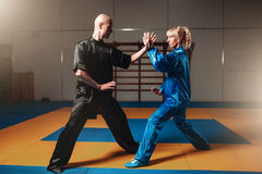 Male and female wushu fighters exercises indoor Stock Image