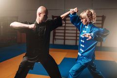 Male and female wushu fighters exercises indoor Royalty Free Stock Image