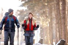 Male and female hikers walking in snowy nature. Male and female young hikers walking in snowy nature Stock Image