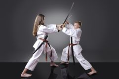 Male and female young karate fighting with swords Royalty Free Stock Image