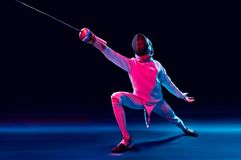 Male fencer in action. Male fencer attacking with a sword isolated on black background Royalty Free Stock Photography