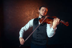 Male fiddler playing classical music on violin. Portrait of male fiddler playing classical music on violin. Violinist man with musical instrument Stock Photography