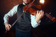 Male fiddler playing classical music on violin. Portrait of male fiddler playing classical music on violin. Violinist man with musical instrument Stock Images