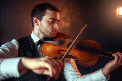 Male fiddler playing classical music on violin. Portrait of male fiddler playing classical music on violin. Violinist man with musical instrument Stock Photos