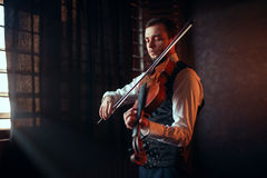 Male fiddler playing classical music on violin. Portrait of male fiddler playing classical music on violin. Violinist man with musical instrument Royalty Free Stock Image