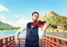 Male fiddler playing classical music on violin. On wooden pier, lake and mountains on background. Violinist man with musical instrument plays on nature Royalty Free Stock Photo
