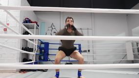 Male fighter jumping while warm up training on boxing ring. Boxer man doing jump exercise in fight club. Sport training. Healthy lifestyle stock footage