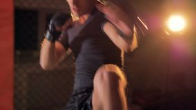 A fighter performs punches and back kicks. A male fighter shows punches, evasions and back kicks under bright light stock footage