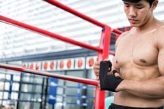 Male fighter wear bandages on fist. muscular man bind bandage on Royalty Free Stock Photo