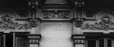 Male figure appearing from the leaves. Shot in black and white, detail on the sculpture on the facade of this historic building representing some characters. Set Royalty Free Stock Photography