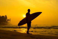 The male figure with a board for surf on a background of ocean w Stock Photos