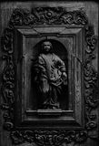 Male figure framed on the wood door. Shot in black and white detail of the sculpture on the facade of this historic building representing some characters / Stock Photography