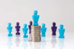 Male figurine placed on top of pile of coins with additional fig Royalty Free Stock Photography