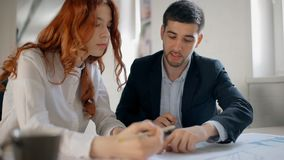 Male financial analytic in suit is discussing financial graphs with his red hair female colleague. Sitting at the office table. Indoors stock video