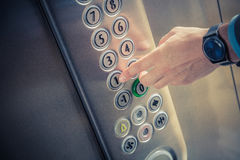 Male finger pressing the first floor button in the elevator. Man pressing the button in the elevator interior Stock Image