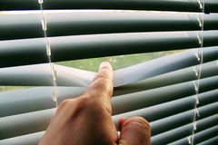 Male finger pushes white horizontal aluminum blinds.  royalty free stock photos