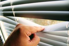 Male finger pushes white horizontal aluminum blinds.  stock image