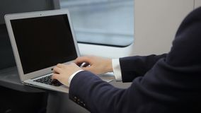 Male fingers of businessman print on laptop keyboard train. Man during travel on transport writes text and presses on touchpad on wireless computer stock video footage