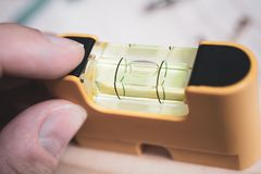 Male Fingers Holding A Small Yellow Spirit Level To Check If The Bubble Is In Center, DIY Home Improvement Concept royalty free stock image