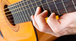 Male fingers playing the guitar Stock Photos