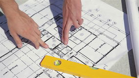 Male fingers point at the plan of the building construction stock video