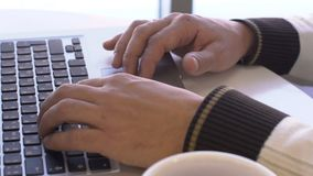 Male fingers press the touchpad and the laptop keyboard. Close-up of a man in sweater is working behind a wireless computer and typing text and is looking for stock footage
