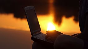 Male Fingers Print on a pc Keyboard Outdoor on a River Bank at Sunset. A Romantic Close-Up of Male Fingers Which Type on a Gray pc Keyboard Outdoor on a River stock video footage