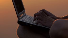 Male Fingers Print on a pc Keyboard Outdoor on a River Bank at Sunset. An Unusual Close-Up of Male Fingers Which Type on a Gray pc Keyboard Outdoor on a River stock footage