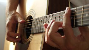 Male fingers touch the strings of an acoustic guitar close-up. Male guitarist playing music. 4K stock video