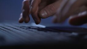 Male fingers typing on laptop keyboard, journalist writing article at night. Stock footage stock footage
