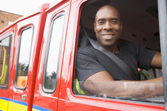 Male firefighter sitting in the cab. Of a fire engine Stock Images